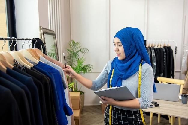 Moslimvrouwenontwerper als start bedrijfseigenaar die in kleermakerswinkel werken