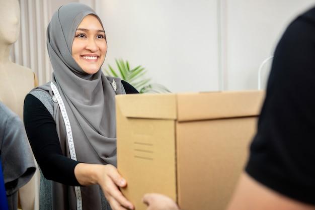 Moslimvrouwenontwerper die pakketdoos van leveringsman ontvangen