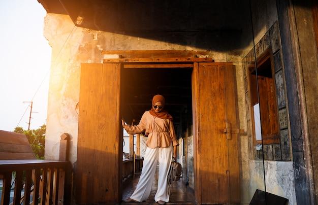 Moslimvrouwentoerist die zich op een trap in een chinese huisatmosfeer bevinden, aziatische vrouw in vakantie. reizen concept. chinees thema.