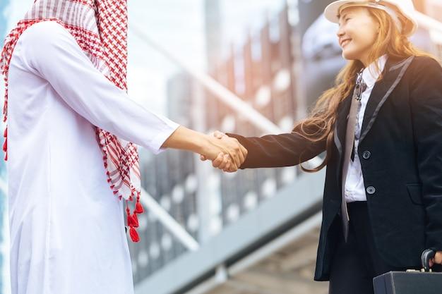 Moslimzakenman en ingenieursvrouw die handen schudden