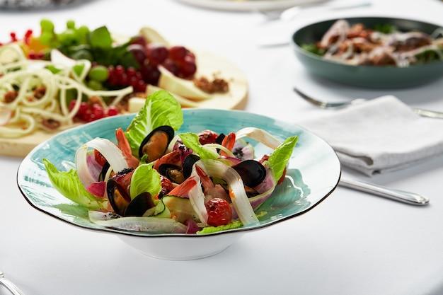 Mosselen gekookt in witte wijnsaus, vongole mosselen in een bord met salade, zeevruchten door de chef.