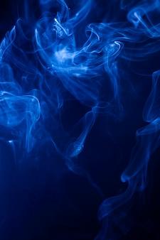 Motie blauwe rook op zwarte achtergrond.