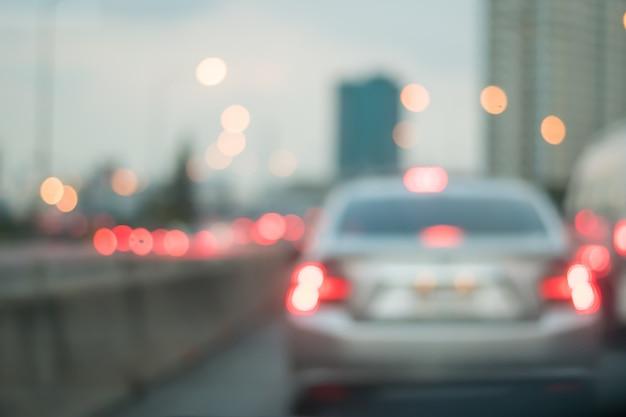 Motieonduidelijk beeld van auto op de weg met abstract licht bokeh in de avond