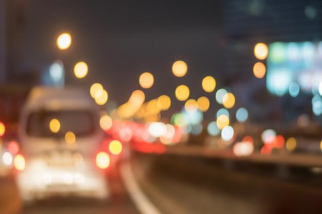 Motieonduidelijk beeld van auto op de weg met abstract licht bokeh in de nacht