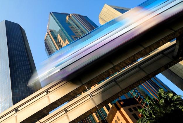 Motieonduidelijk beeld van een skytrain die door een modern bedrijfsdistrict snijdt