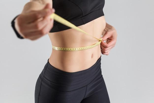 Motivatie concept perfecte maag vrouw met centimeter en glimlachend grijze achtergrond