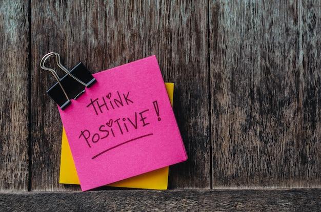 Motivatie denk positieve slogan notitieblokken en paperclip op oude houten achtergrond