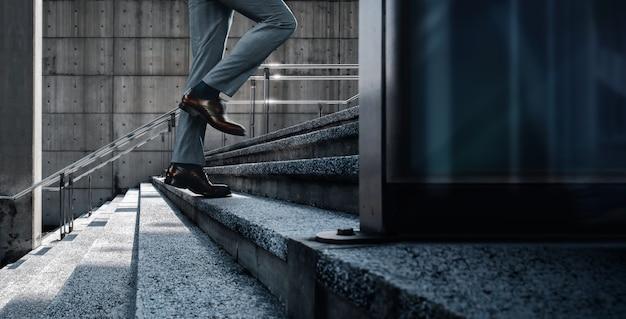 Motivatie en uitdagend concept. stappen vooruit naar een succes. lage sectie van zakenman die op de trap loopt. stadsscène