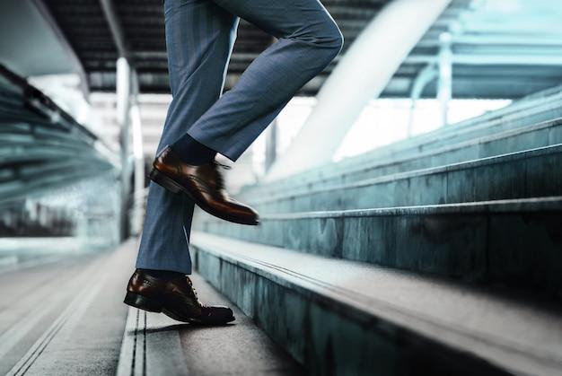 Motivatie en uitdagend concept. stapt vooruit in een succes. lage sectie van zakenman lopen op trap