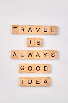 Motivatiecitaat voor reizen. reizen is altijd een goed idee. reisconcept geschreven met houten blokken op witte achtergrond.
