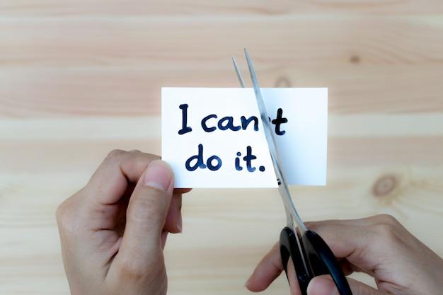 Motivatieconcept, vrouwenhanden die kaart houden die ik het met schaar kan doen.