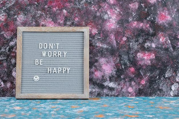 Motiverende citaat ingebed op een grijs bord. maak je geen zorgen, wees blij