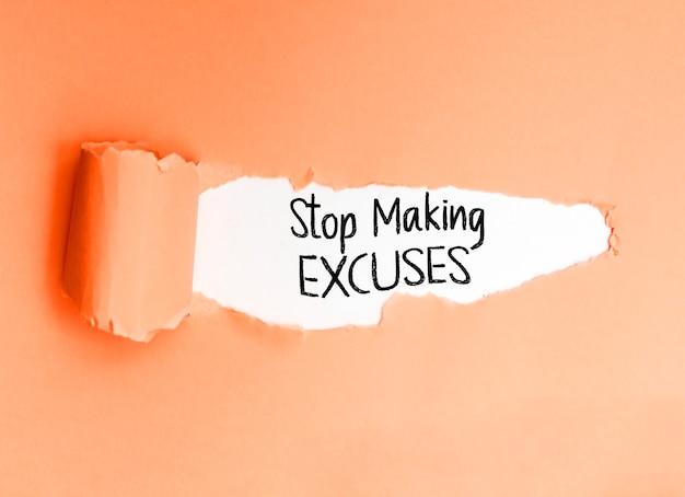 Motiverende zin stop met het maken van excuses, geschreven op een gescheurd papier