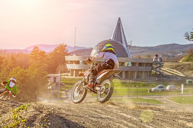 Moto cross biker op race - een scherpe bocht en de spray van vuil, achteraanzicht - close-up