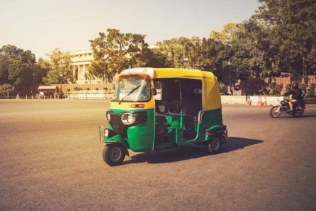 Moto-riksja, new delhi, india. indiase taxi staat op straat tegen de achtergrond van het presidentiële paleis. dure wijk van de stad. driewieler vintage retro motorfiets 50-60 van de 20e eeuw