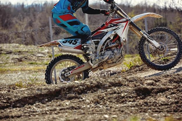 Motocross-coureur in actie versnellen van de motor stijgt op en springt op de springplank op het circuit