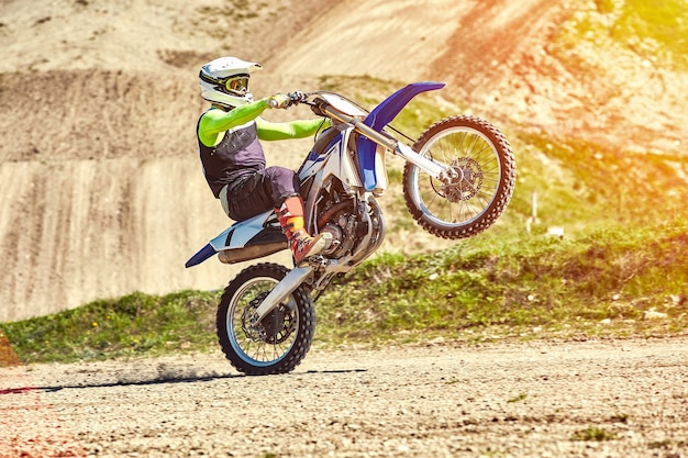 Motocross, een rijder staat op het achterwiel van een fiets rijden op het achterwiel extreem industriële crosscountry motorrijden voor extreem.