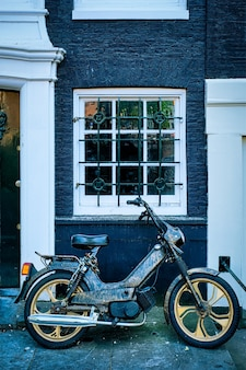 Motor geparkeerd in de buurt van oud huis in de straat van amsterdam