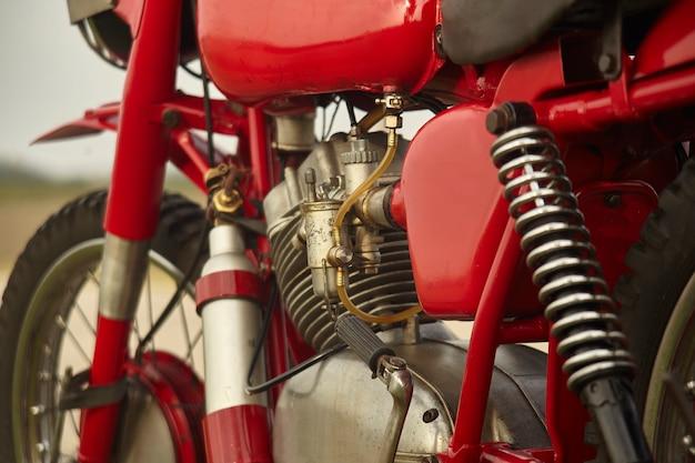 Motor van een zeer oude vintage motorfiets met zichtbare details van de ophanging, de carburateur en diverse andere mechanische onderdelen.