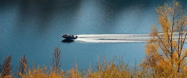 Motorboot beweegt in het midden van de blauwe rivier die tussen de heuvels met herfstbos stroomt.