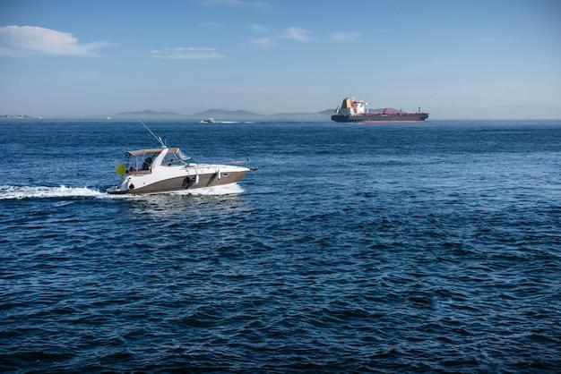Motorboot en een vrachttanker in de zwarte zee