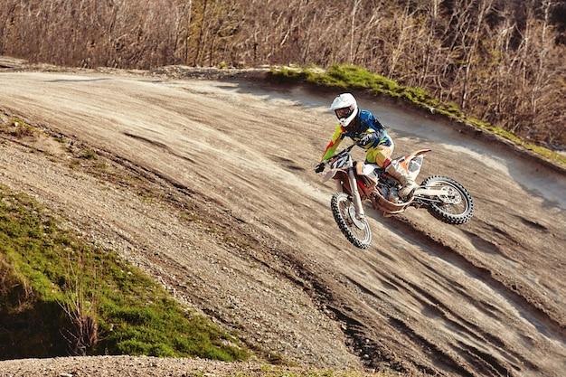 Motorcross-concept, een motorrijder gaat off-road en maakt extreem skiën. bij het nastreven van adrenaline, sportconcept. gevaarlijke sporten.