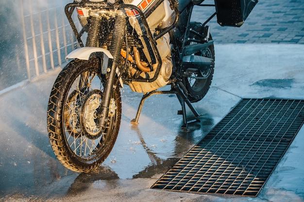 Motorcycle car wash. een serie foto's van een motorrijder die zijn motorfiets wast bij de carwash. vervoer-