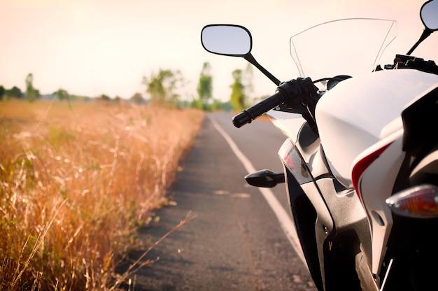 Motorfiets die op landweg reizen tegen mooi licht van zonsonderganghemel