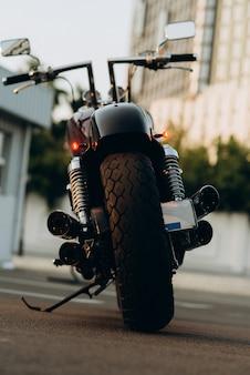 Motorfiets op de parkeerplaats, achteraanzicht. bandenprofiel en chromen uitlaatpijpen. stijlvolle custom chopper motobike met chromen onderdelen. zachte selectieve focus.