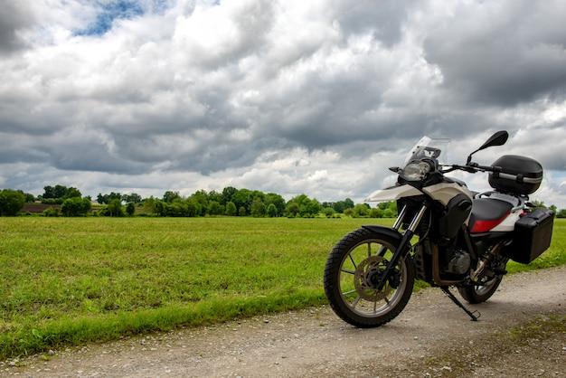 Motorfiets op een pad met een bewolkte hemel