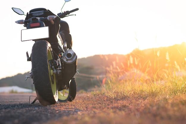 Motorfiets parkeren op de weg, vintage stijl met zonsonderganglicht, kopie specificatie voor individuele tekst, motor met natuurlandschap