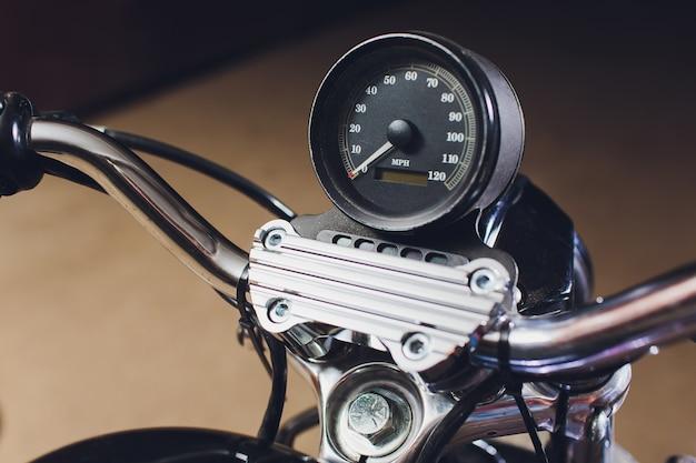 Motorfietsen op de vloer met werkplaatsgereedschap, een moderne garage, opslag en reparatie. deze fiets zal perfect zijn. repareren van een motorfiets in een reparatiewerkplaats. snelheidsmeter close-up