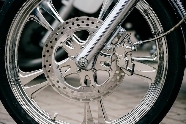Motorfietswiel met schijfremsysteem en metalen spaken. close-up gedetailleerde foto van motorvorken en band.