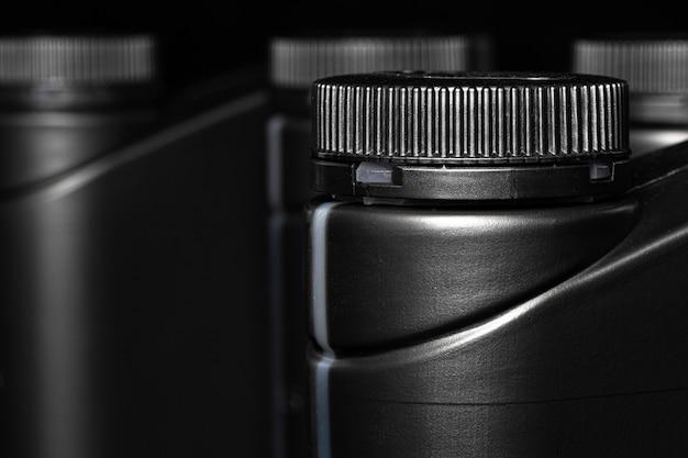 Motorolie fles op zwarte achtergrond, close-up.