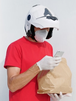 Motorrijder bezorger in uniform. houdt een papieren zak in medische beschermende handschoenen en een kn95-masker, kijkend naar mobiel.