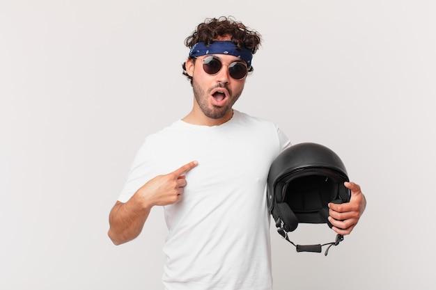 Motorrijder die geschokt en verrast kijkt met wijd open mond, wijzend naar zichzelf