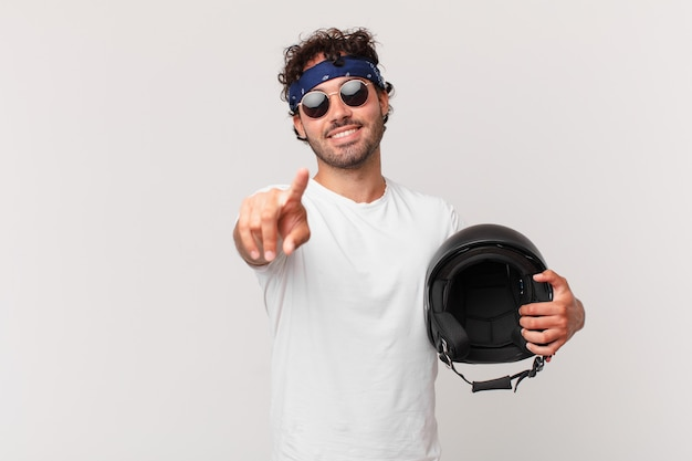 Motorrijder die met een tevreden, zelfverzekerde, vriendelijke glimlach op de camera wijst en jou kiest