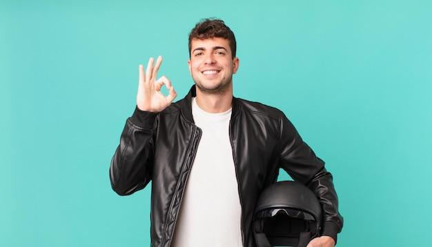 Motorrijder die zich gelukkig, ontspannen en tevreden voelt, goedkeuring toont met een goed gebaar, glimlachend
