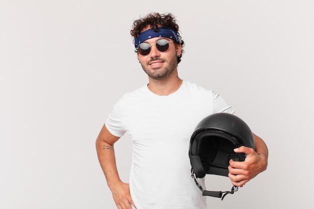 Motorrijder glimlachend gelukkig met een hand op de heup en zelfverzekerde, positieve, trotse en vriendelijke houding