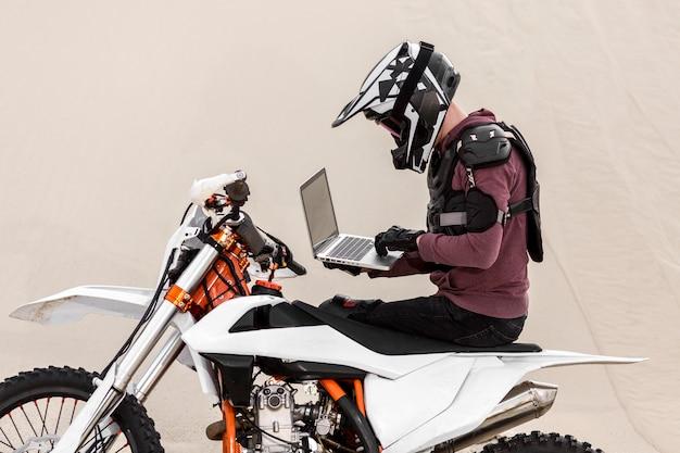 Motorrijder het doorbladeren laptop in de woestijn