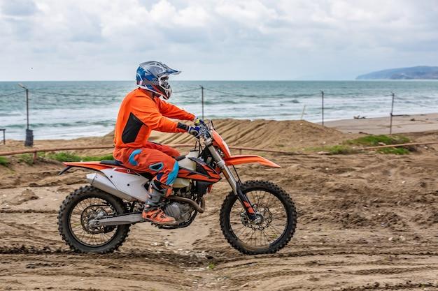 Motorrijder in een beschermend pak op motor voor de zee