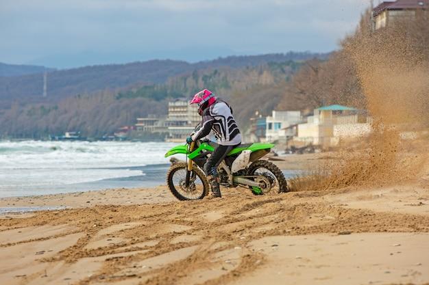 Motorrijder in een beschermend pak rijdt op een motorfiets op zee, spatten vliegen van onder de wielen.
