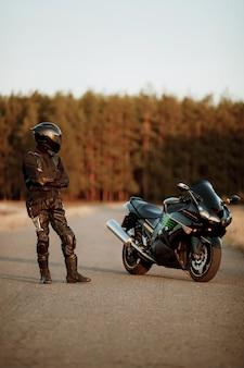Motorrijder in een helm en een leren jas staat op de weg bij zonsondergang met een prachtig bos achtergrond en kijkt naar een sportieve motorfiets