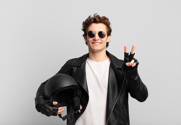 Motorrijder jongen lacht en ziet er vriendelijk uit, toont nummer twee of seconde met de hand naar voren, aftellend
