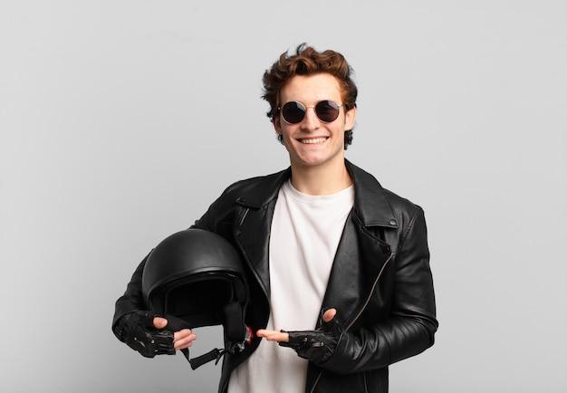 Motorrijder jongen lacht vrolijk, voelt zich gelukkig en toont een concept in kopieerruimte met palm van hand