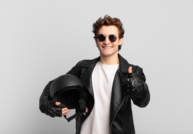 Motorrijder jongen voelt zich trots, zorgeloos, zelfverzekerd en gelukkig, positief glimlachend met duimen omhoog