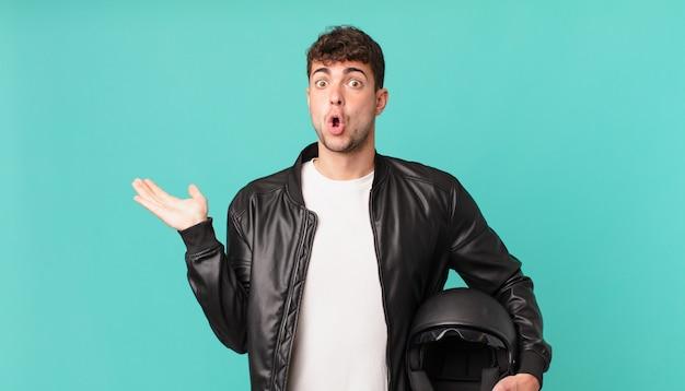 Motorrijder kijkt verrast en geschokt, met open mond terwijl hij een object vasthoudt met een open hand aan de zijkant