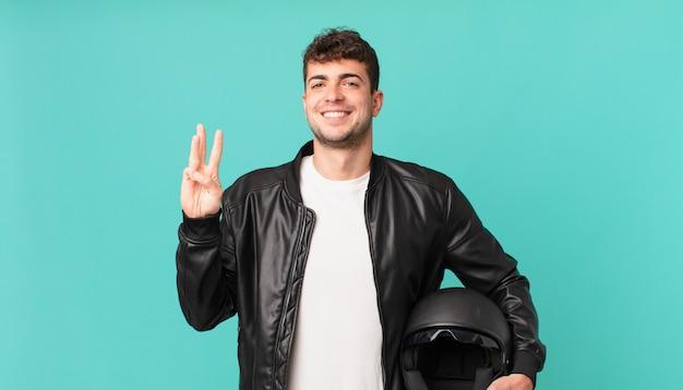 Motorrijder lacht en ziet er vriendelijk uit, toont nummer drie of derde met hand naar voren, aftellend