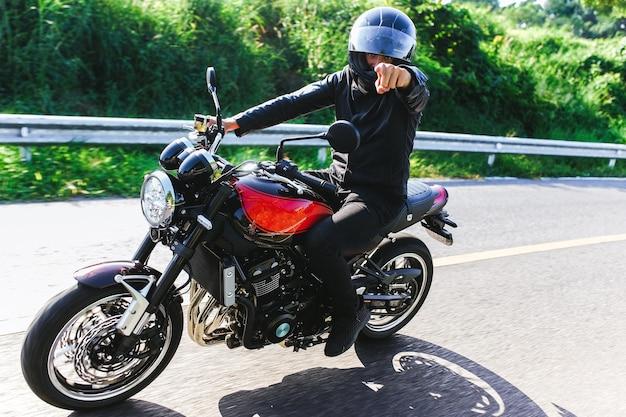 Motorrijder met helm rijdt op zijn zwart-rode motorfiets en wijst naar de camera actiefotografie