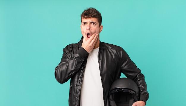 Motorrijder met mond en ogen wijd open en hand op kin, onaangenaam geschokt, wat zeggend of wauw